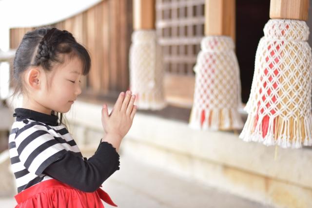 神社で参拝する女の子